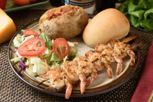 Grilled shrimp with freshly-baked potato, crisp salad and fresh dinner roll